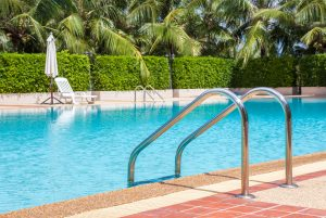 A view of clear blue swimming pool with steel ladder